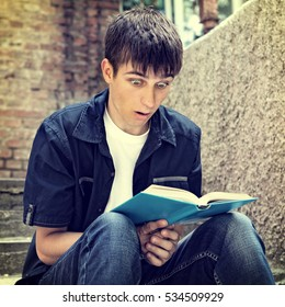 Toned Photo of Surprised Teenager with the Book on the City Street