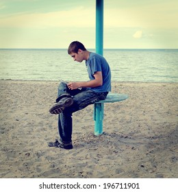Toned photo of Teenager reading the Letter on the Empty Beach