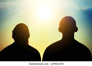 Toned Photo of Two Friends silhouette on evening sky background