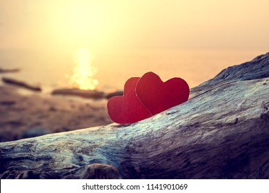 Toned Photo of Two Red Hearts at the Evening Beach