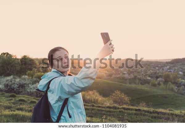 Toned photo of the young female traveller making a selfie with her smartphone on the sunset. Concept of the vacation, travel, enjoyment, blogging, vlogging.