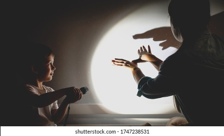 Toned photo of young mother and little boy playing in theater of shadows before going to sleep at night.