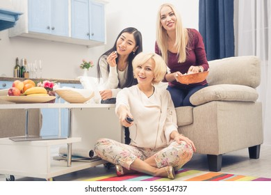 Toned picture of best friends girls watching interesting films or movies on television while having party in kitchen at home. Pretty ladies looking at camera.