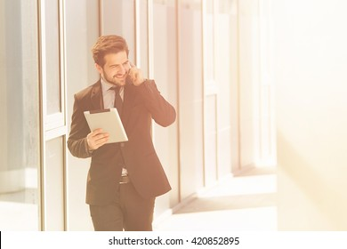 Toned picture of businessman in black suit speaking over mobile or smart phone with business partners. Handsome man hurrying to work.