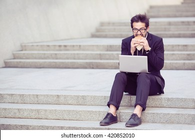 Toned picture of businessman eating hamburger during his work in city cente as freelancer. Handsome man in business suit working on laptop computer.