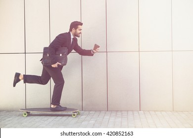 Toned picture of businessman on longboard and with cup of coffee going to office. Freelance man in black business suit hurrying.