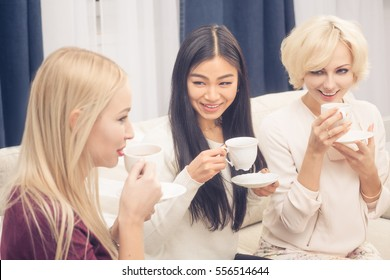 Toned picture of friends girls drinking delicious tea all together and communicating. Pretty ladies having party at home after hard working day or week.