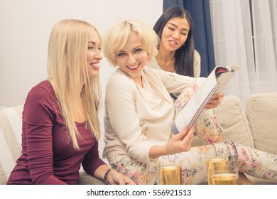Toned picture of friends girls spending free time at home. Beautiful ladies drinking champagne, smiling and reading magazines. Home party concept.