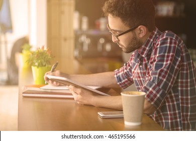 Toned picture of handsome student man studying in restaurant or cafe. Man using tablet PC for writing essay or publication.