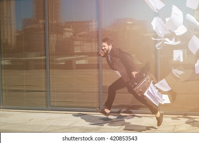 Toned picture of running businessman along street with briefcase and speaking over mobile or smart phone. Freelance man in hurry.