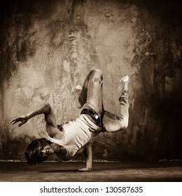 Toned picture of young man  doing acrobatic movements against grunge wall