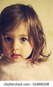Toned portrait of beautiful sad toddler girl thinking