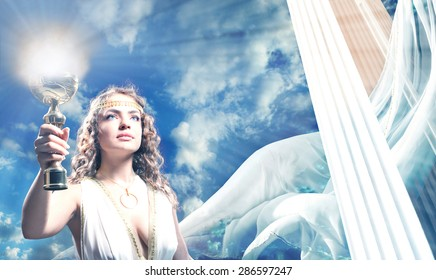 Toned Portrait of The Beautiful Young Woman Holding a Gold Goblet of Flame in the Blue Sky. She is Wearing the White Greek Tunic.