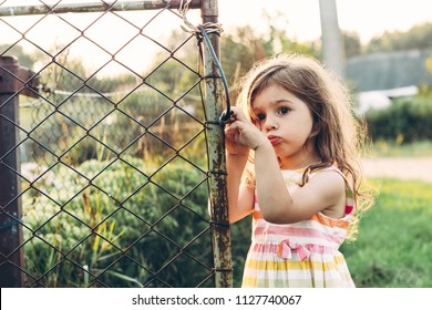 Toned portrait of a Cute little girl looking sad standing near the wire fence