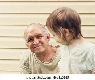 Toned portrait of Happy grandfather and granddaughter playing at yard