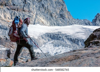 Toned Portrait of Nepalese professional Mountain Guide staying on Rock and looking up at high Altitude Summits and Glacier carrying Backpack with alpine climbing Gear
