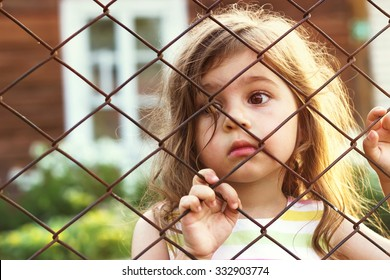 Toned portrait of Sad cute little girl looks through wire fence