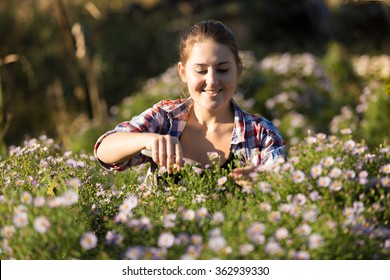 Toned portrait of young woman cutting flowers at garden