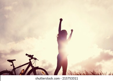 Toned portrait of young woman with raised hands over sunbeams