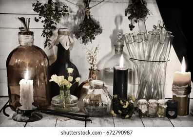 Toned still life with alchemical bottles and jars, burning candles and healing herbs. Alternative medicine, old pharmaceutic and homeopathic concept. Mystic and occult still life, vintage background