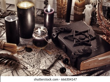 Toned still life with black magic book, demon paper and black candles. Halloween concept. Mystic background with occult and magic objects on witch table.