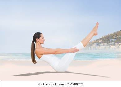 Toned woman doing the boat pose in fitness studio against beautiful beach and blue sky