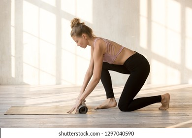 Toned young woman roll rubber mat after good yoga practice in fitness studio, sportive female yogi fold sport facility after training or workout, fit girl finish pilates class. Healthy life concept