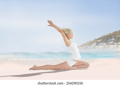 Toned young woman stretching hands backwards against beautiful beach and blue sky
