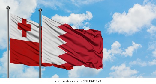 Tonga and Bahrain flag waving in the wind against white cloudy blue sky together. Diplomacy concept, international relations.