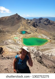 Tongariro national park / New Zealand - 12 28 2015: young blonde backpacker girl posing with emerald lakes on famous Tongariro Alpine Crossing hiking trail, popular place for tourists and hobbit fans