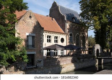 TONGEREN, BELGIUM - SEPTEMBER 13 2020: Cityscape of Tongeren, the oldest city in Belgium, on the river de Jeker with restored houses, bridge and restaurant