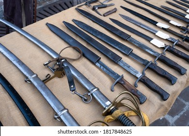 TONGEREN, BELGIUM - SEPTEMBER 13 2020: All kinds of swords with scabbards in different sizes displayed on a table for sale on an antique market in Tongeren, Belgium