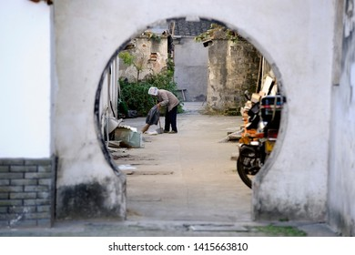 TONGLI, CHINA- NOVEMBER 28, 2008: Old lady street sweeper cleaning the street in a hutong of the town