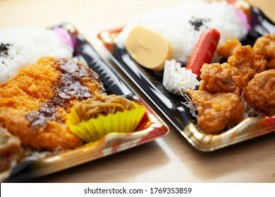 Tonkatsu bento and fried chicken bento in a plastic container