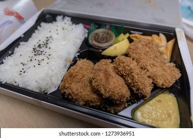 Tonkatsu Bento Served with Japanese Rice Wraped, Cut Tonkatsu (Deep Fried Pork Cutlet) - image