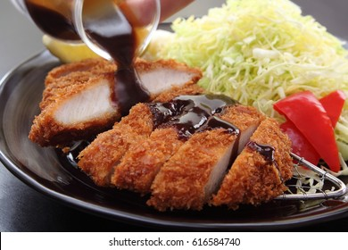 Tonkatsu is a Japanese dish which consists of a breaded, deep-fried pork cutlet./ Deep Fried Pork Loin Cutlet with Salad and Lemon, Japanese Food