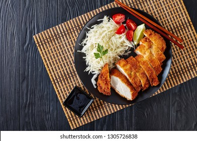 Tonkatsu - panko breaded deep-fried pork cutlet served with fresh shredded cabbage salad, tomatoes and lime slices on a black plate on a bamboo mat, Japanese cuisine, view from above, flatlay
