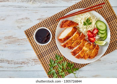 Tonkatsu - panko breaded deep-fried pork cutlet served with fresh shredded cabbage salad, tomatoes and lime slices on a plate on a bamboo mat, Japanese cuisine, view from above, flatlay