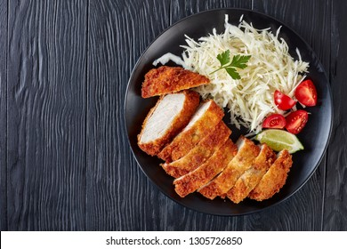Tonkatsu - panko breaded deep-fried pork cutlet. Deep Fried Pork Loin Cutlet with fresh cabbage Salad, tomatoes and lime slices, Japanese cuisine, flatlay, view from above, copy space