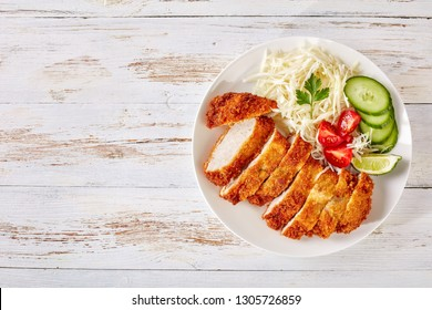 Tonkatsu - panko breaded deep-fried pork cutlet served with fresh shredded cabbage salad, tomatoes and lime slices on a plate, Japanese cuisine, view from above, copy space