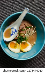 Tonkatsu ramen bowl with soft boiled eggs, enoki mushrooms and pork belly in a blue bowl with ceramic spoon.