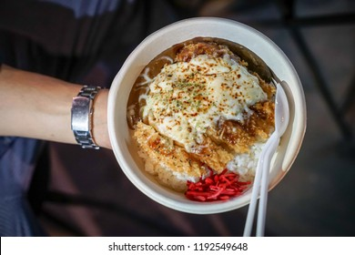 Tonkatsu; traditional Japanese food, crispy fried pork with sauces on top and rice under it, in the paper dish. Food street of Bangkok, Thailand.