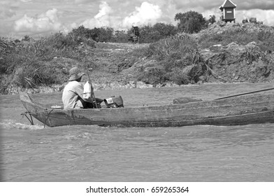 TONLE SAP, CAMBODIA - JUNE 14 2013: Unidentified man drive a boat at Tonle Sap lake, near Siem Reap, Cambodia.