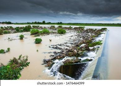 Tonle Sap River Dam spillway overflow on a rainy day, dark storm is coming. Cambodian floodplain, Phnom Penh, Cambodia.