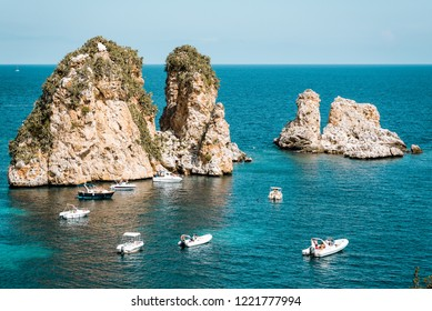 Tonnara di Scopello in Sicily, Italy. Boats with tourists floating near the cliffs.
