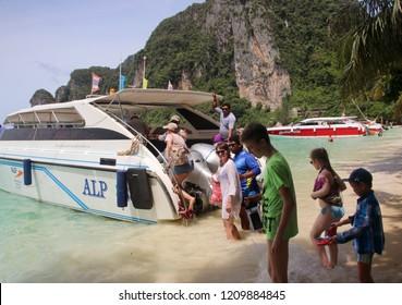 TONSAI BAY, PHI PHI DON ISLAND, THAILAND - JULY 15, 2018: Unidentified tourists go aboard a tourist speedboat in Tonsai Bay, Koh Phi Phi Island, Thailand