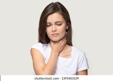 Tonsillitis angina concept image head shot studio portrait on grey background unhealthy woman touch neck feels discomfort painful feelings hard to swallow, sore throat pain irritation or loss of voice