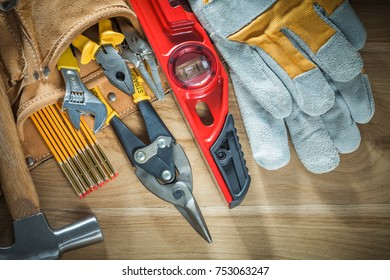 Tool belt with tooling construction level protective gloves on wooden board.