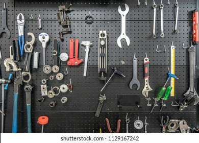 The tool hangs on a black wall. Organized and clean in the shop.