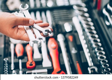 Tool hardware store. Closeup of male hand holding wrenches and spanners. Auto repair kit in toolbox. Repairman instruments set.